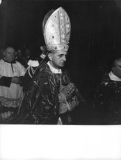 Pope Paul VI standing with hands joined.