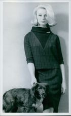 Woman standing with a dog.