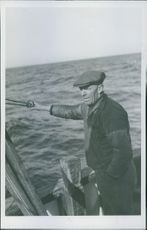 1945 Fisherman standing on a boat.