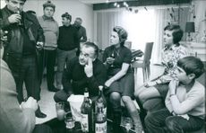 Men and woman drinking in the home, children siting.
