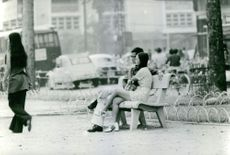 A man and a lady in the park sitting and talking at the bench in Vietnam. November 16, 1972