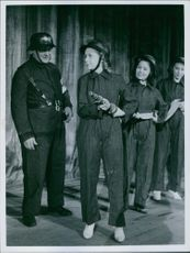 Woman soldiers standing together and talking to a man standing beside them and smiling.