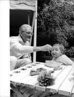 A photo of Michelle Bardot's son Nicolas-Jacques Charrier is being  fed by his grandfather Louis Bardot.