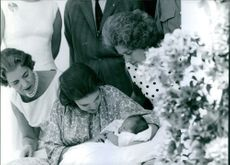 Women sitting, holding her new born baby in her arms, other women standing beside looking at the baby and smiling.