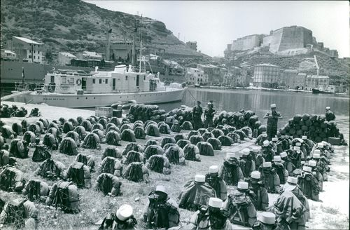 Luggage of soldiers at port, soldiers guarding.