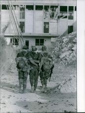 Two soldiers assisting their wounded comrade to walk. 1961.