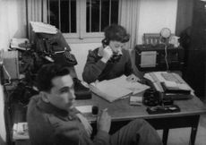 Woman on her desk talking on the telephone with a policeman holding a cigarette looking at the camera, in Israel.