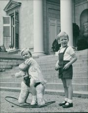 Two children playing and looking on camera.