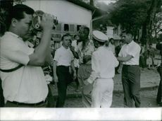 A wounded and bloody man in the street with people around watching him and a photographer taking pictures, in Saigon, Vietnam, 1965.
