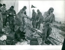 Soldiers gathered and eating, one is communicating using a radio in Algeria.  - Apr 1959
