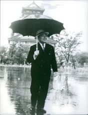 A portrait of Admiral Kusaka walking outdoor while holding an umbrella on a rainy day.
