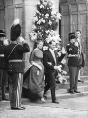Princess Irene of the Netherlands with her husband Duke Carlos Hugo walking through outside the royal palace.