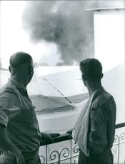 Two man are seeing the blast of a bomb