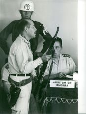 Man standing with gun, few sitting beside.