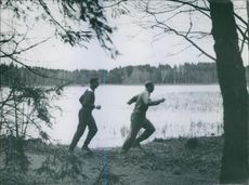 A photo of two man running beside the river.