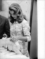 Lee Ann Remick checking clothes.