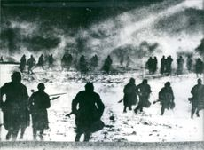 Russian soldiers cross a snowy filed near Moscow in the winter of 1941-1942, in an attack on a German position. 1982.