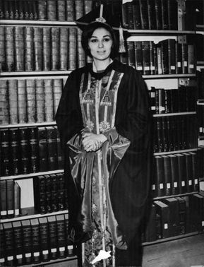 Farah Pahlavi wearing an academic dress in a library.