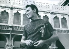 Jack Palance standing in front of a building.