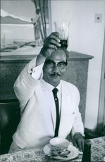 Man lifted up a glass in his hands, looking towards the camera and smiling.