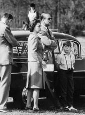 Quenn Elizabeth II, Prince Philip and Prince Andrew standing in fron of a car.