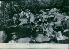 The natives by the Pacific Ocean are helping the American Soldiers carrying ammunition and food to the troops.