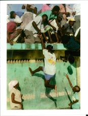 Rwanda war:haitians try to scale the walls of compound.