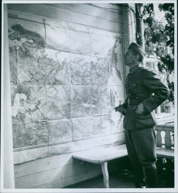 Soldier standing holding stick in his hands and looking at the map outside office.  1941 office
