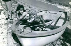 Andréa Parisy striking a pose on the boat parked on seashore, 1964.