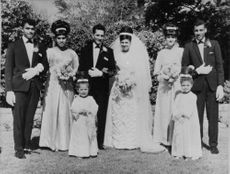 Newly wed couples standing in a row, posing for a photograph.