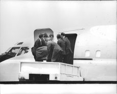 People lifting coffin from hoist on to air plane.