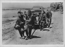 A group of soldiers pulling a vehicle.