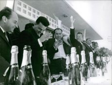 A photo of men standing in line during a competition of wine drinking.  1966