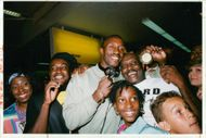 Linford Christie happily holding a medal with other people.