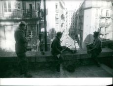 Soldiers patrolling city from balcony.