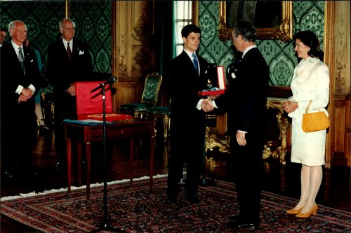 Prince Carl Philip receives the insignia of the Seraphim Order by his father King Carl Gustaf