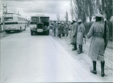 Soldiers guarding and checking up the vehicles on road.
