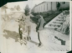 Soldier riding in donkey in street and talking to a boy and smiling. Photo taken in 1935 during the Franco-Turkish War.
