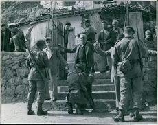 Soldiers checking people in front of a gate.