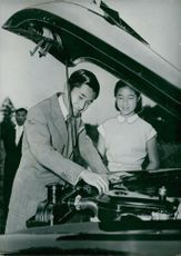 Crown Prince Akihito with his sister Princess Suga. Here the prince mocks his car with his hood open.