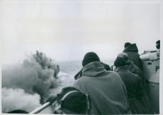 People looking at bomb locations near their ship while at sea.  - 1940