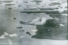 Year ? Puffs of smoke rise after American bombers drop their loads on the Japanese base to the American stronghold.