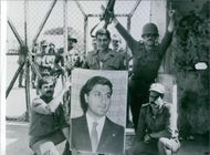 Soldiers of the right-wing Fallangists(Christian Militia) led by newly elected president Gemayel, celebrating his election with the V for victory sign and displaying his portrait to camera. 1982