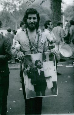 A hippy holding a picture of him holding a banner with a written statement on it.