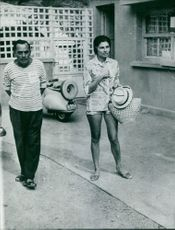 Princess Soraya holding hat and standing with man.