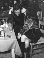 Pascale Petit sitting with man at party..