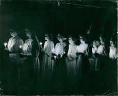 Nuns standing and doing spiritual activity, holding candles.