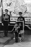A little boy standing in front of the royal chair in a formal ceremony.