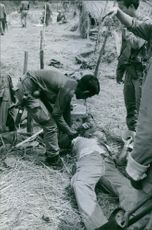 Soldiers trying to help an injured man lying on the ground during Laos war, 1970.