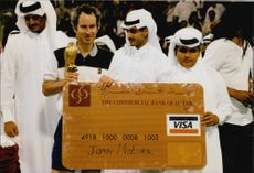 John McEnroe receives a VISA card by Shaikh Tamim after winning the Qatar tennis tournament